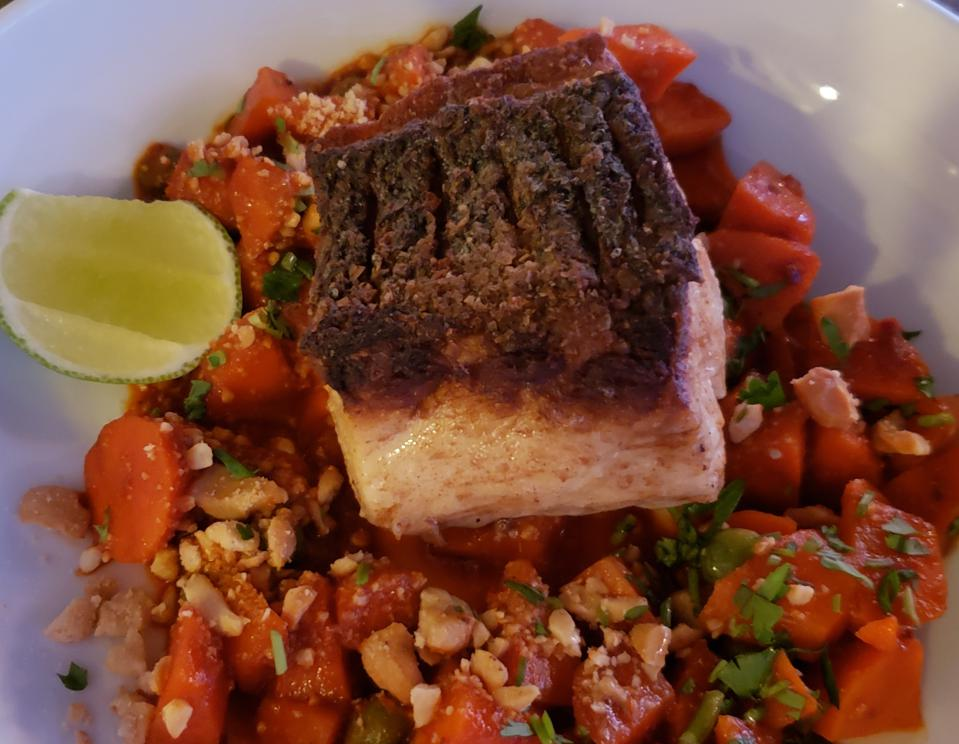 A crispy fish on a bed of carrots, cashews and cilantro