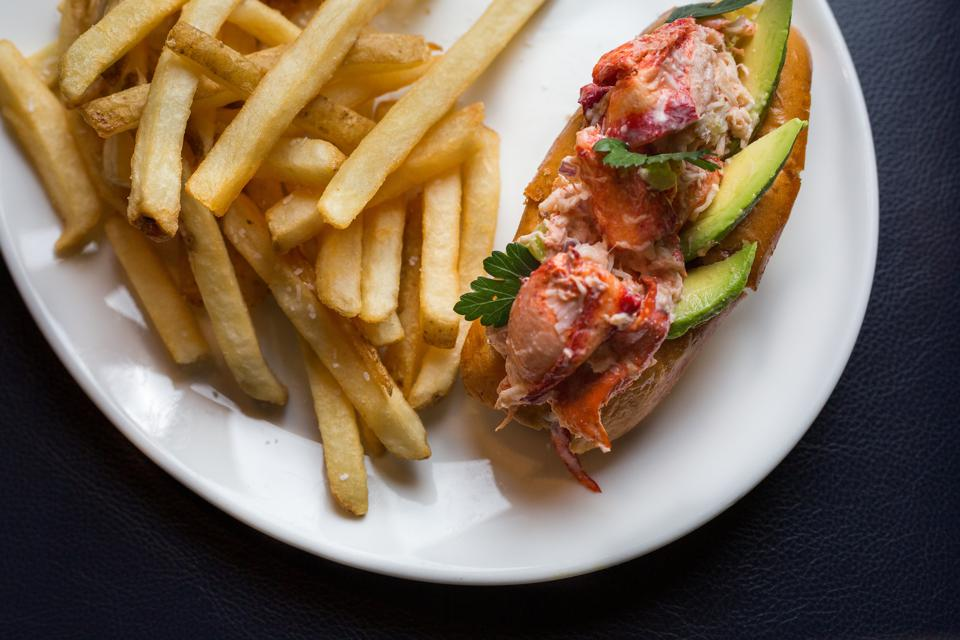 A lobster roll with french fries