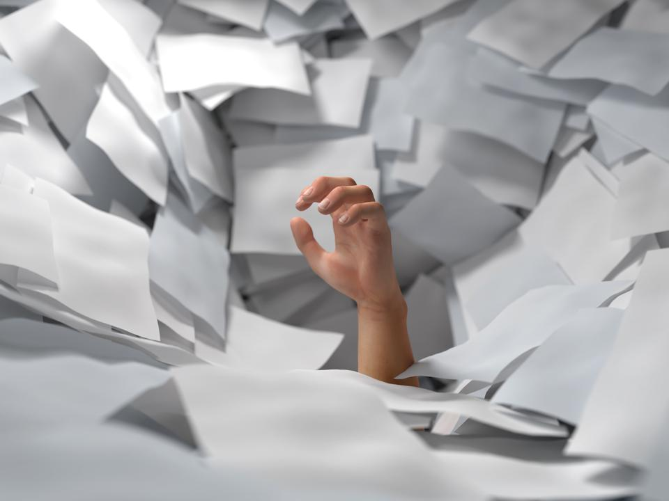 Person drowning in paper