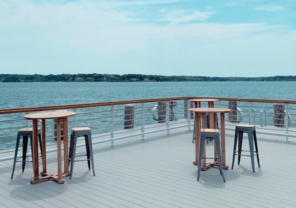 High top tables on a pier overlooking the harbor