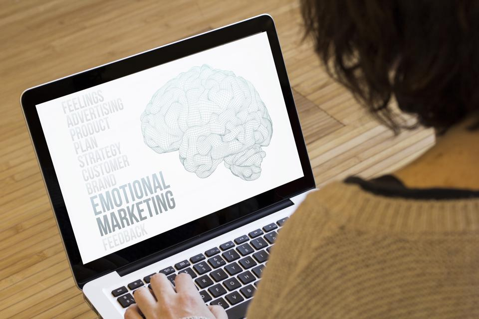 Woman looking at a laptop screen and seeing a brain and the words: Emotional Marketing.