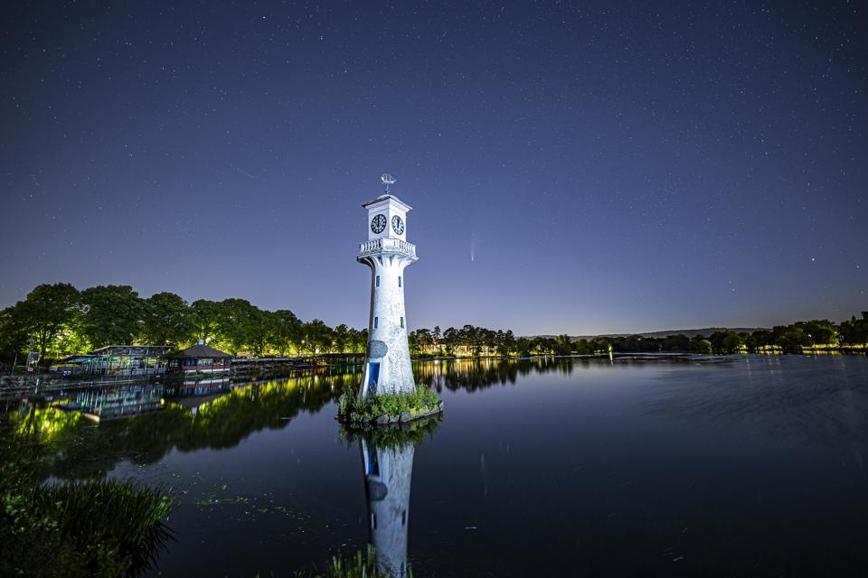 La cometa NEOWISE si riflette nel lago Roath Park a Cardiff, nel Galles.  La torre dell'orologio è un monumento commemorativo dal 1913 a Scott e alla spedizione antartica britannica del 1910, che partì da Cardiff.