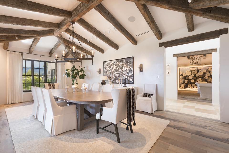 Upscale dining room with white chairs, wood beams on ceiling