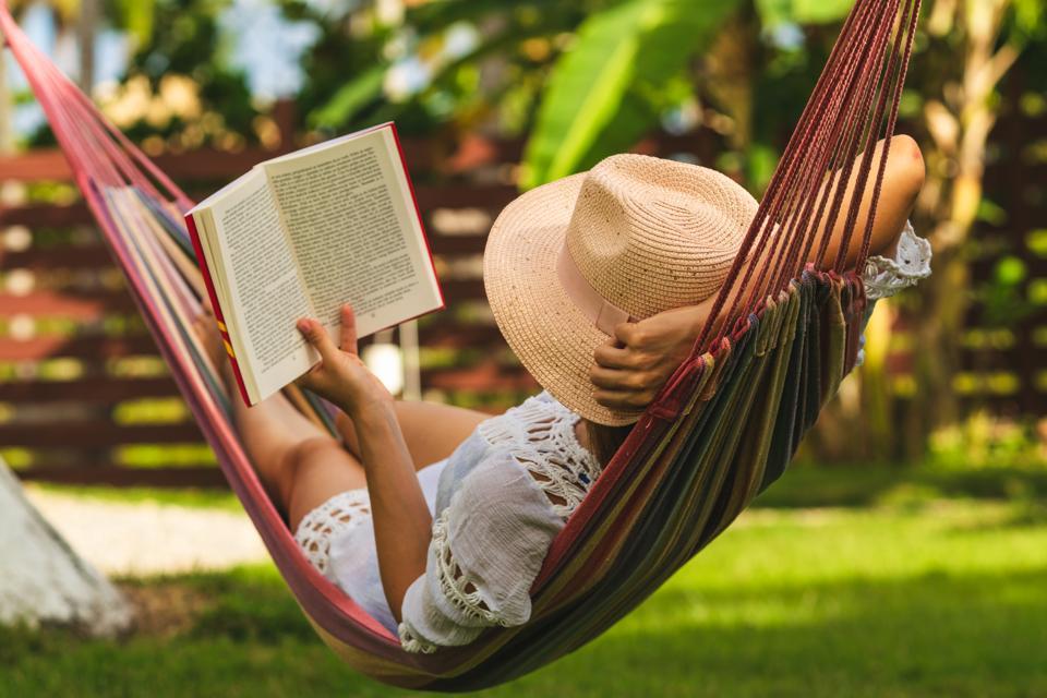 Woman reading book in hammock.