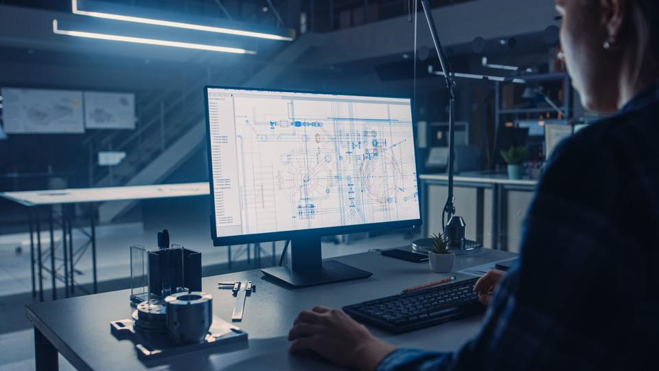 Engineer Working on Desktop Computer, Screen Showing CAD Software with Technological Blueprints. Industrial Design Engineering Facility. Over the Shoulder Shot