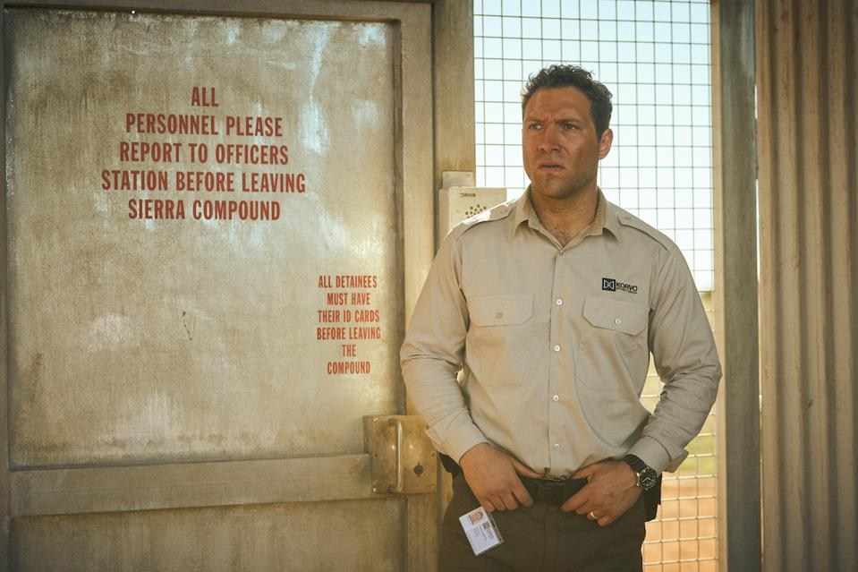 Jai Courtney as Cam Sandford, a security guard at an Australian detention center.