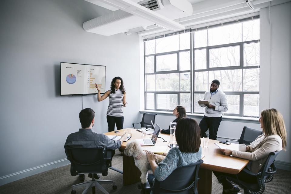 Businesswoman explaining data to colleagues in meeting at board room