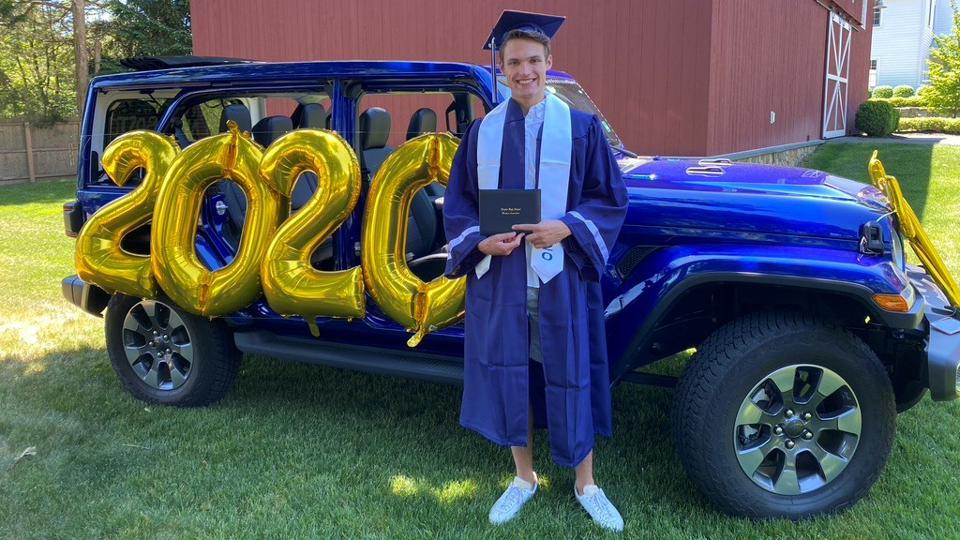 A high school graduate stands in front of a car decorated with large 2020 balloons from Party City.