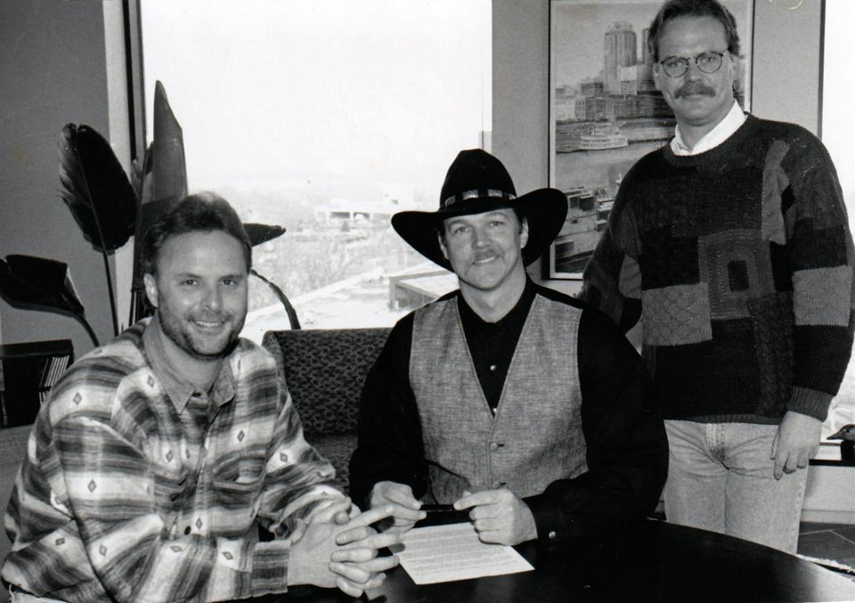 Scott Hendricks sits with Trace Adkins after signing him to Capitol Records Nashville