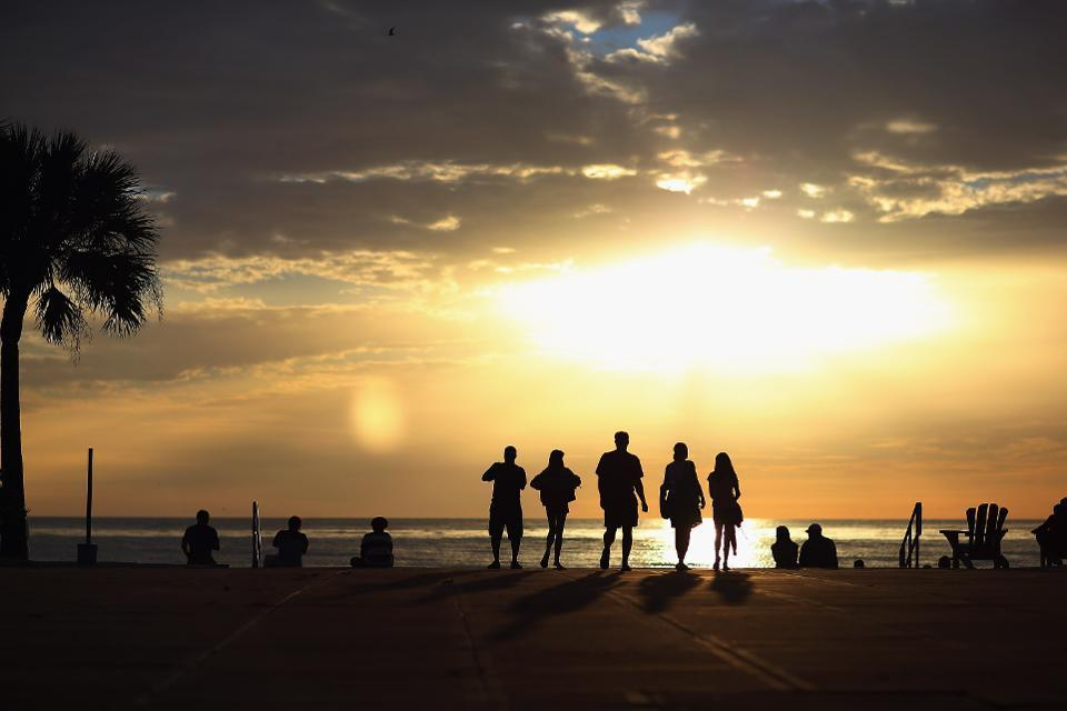 Five people silhouetted as the sun sets on beach