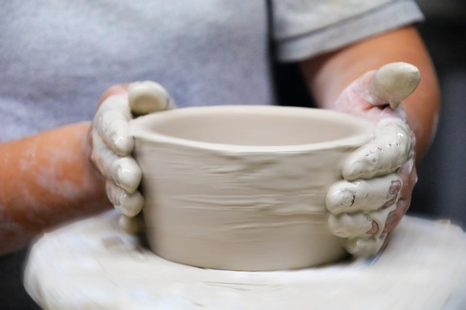 A potter hard at work sculpting the base of a Clase Azul GOLD bottle.