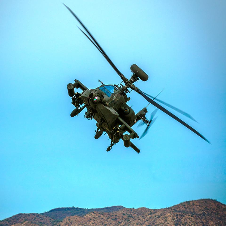 The AH-64 Apache banks left over the desert.