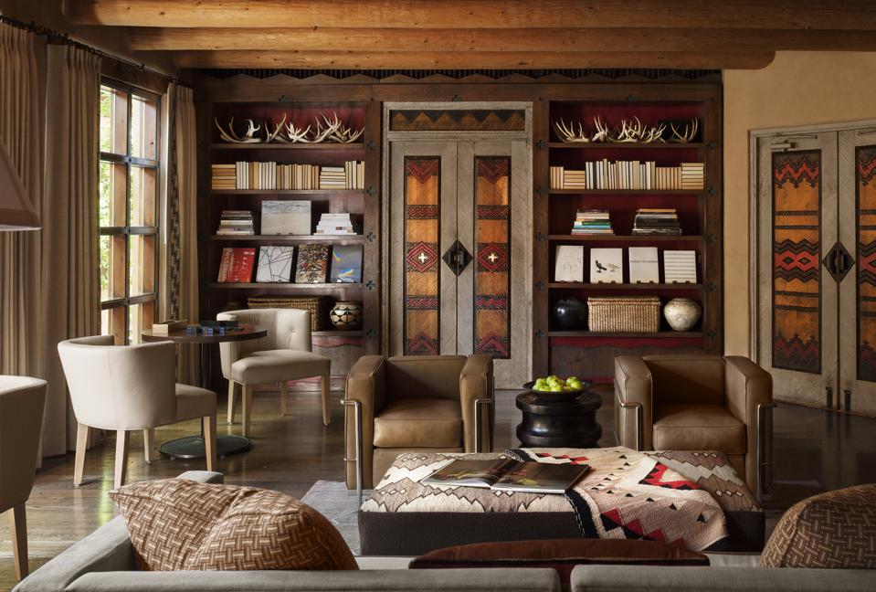 A room with books and Southwestern designs and artifacts at the Santa Fe hotel Rosewood Inn of the Anasazi
