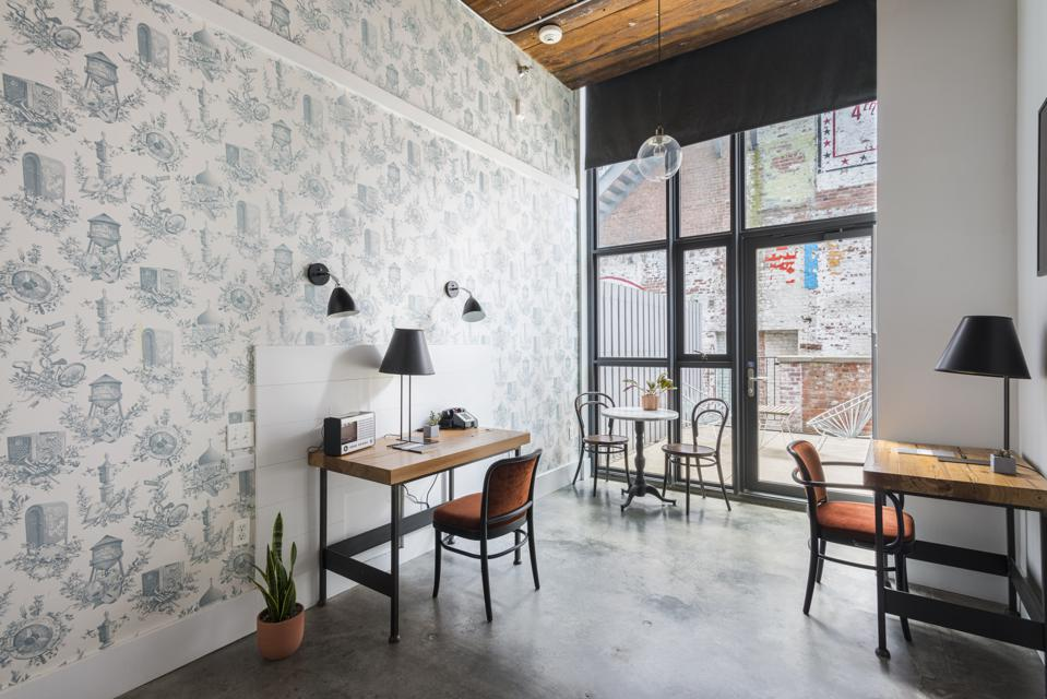 A room with two contemporary desks and an outdoor deck at Brooklyn's Wythe Hotel.