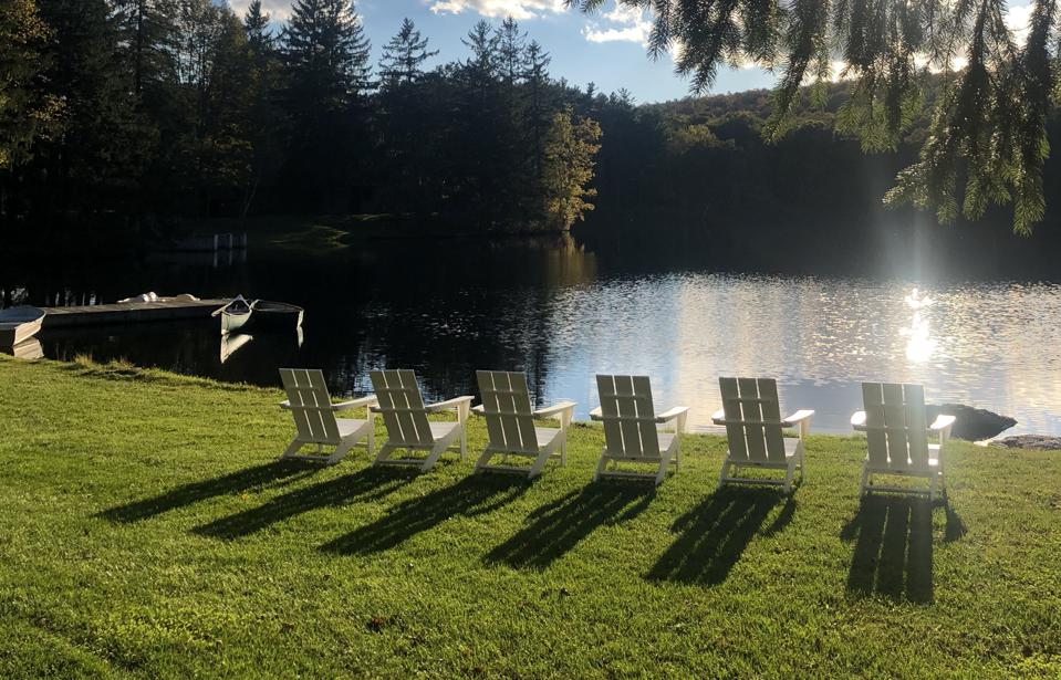 Adirondack chairs lined up overlooking a lake