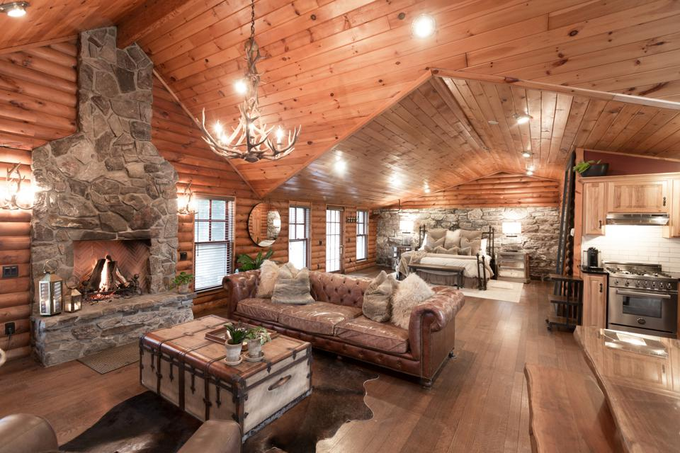 A wood lined cottage interior with stone fireplace