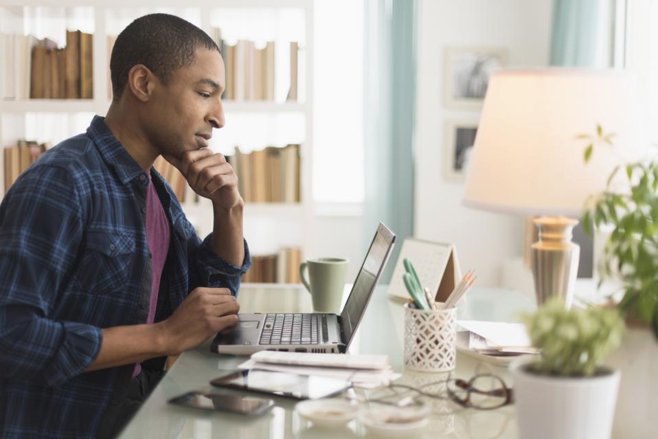 Uomo d'affari nero che lavora al computer portatile allo scrittorio