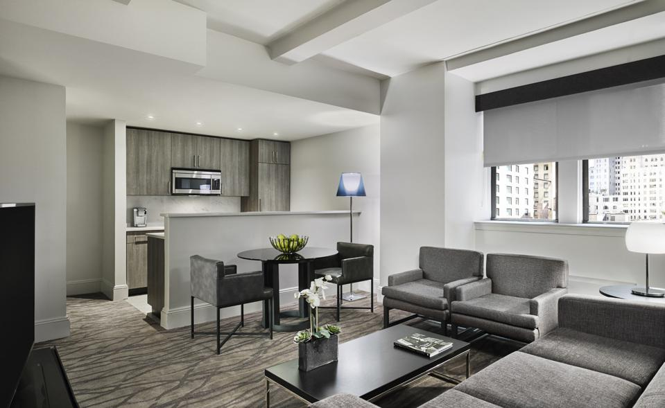 A hotel suite living room filled with grey, contemporary furnishings.