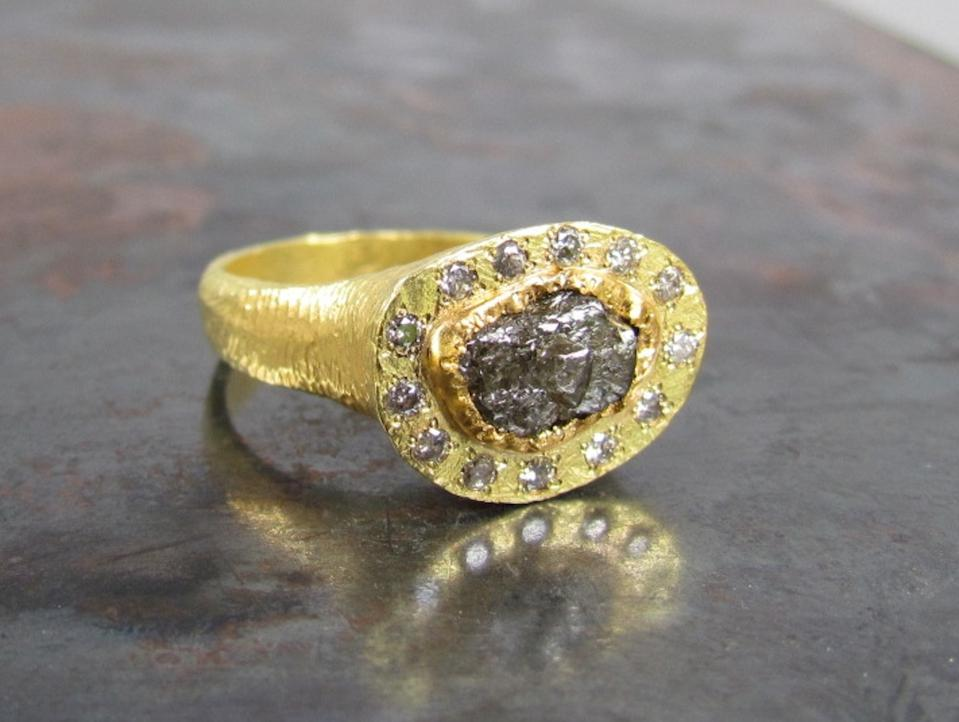 A black rough diamond ring with diamond halo, set in 18kt gold by Anna Ben Ruby.