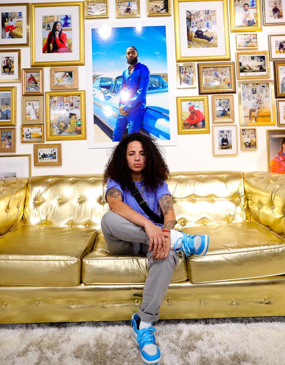 Paola Fernandez chilling on a gold couch and photographs on the wall behind her