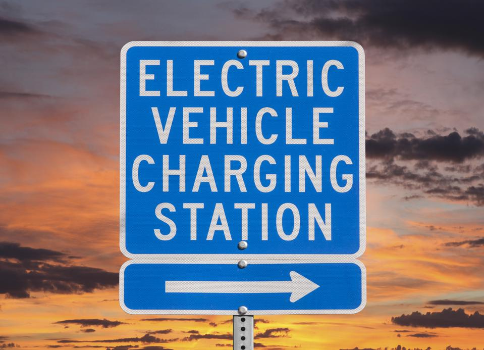 Blue electric vehicle charging station wayfinding signage outlined by a sunset sky