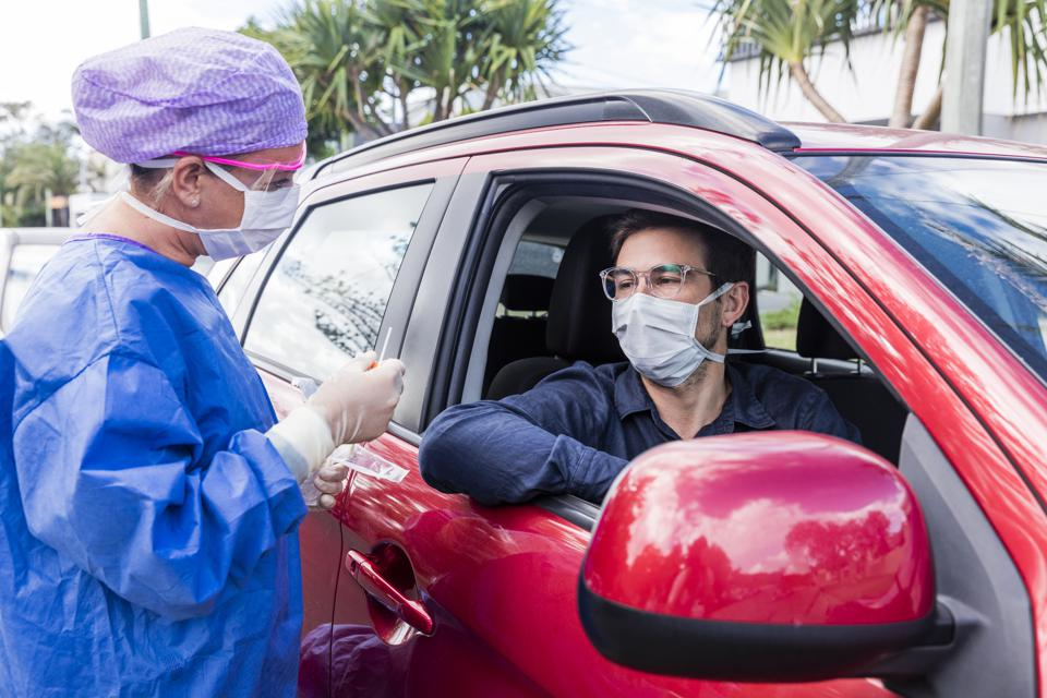 A doctor taking a nasal swab from a driver