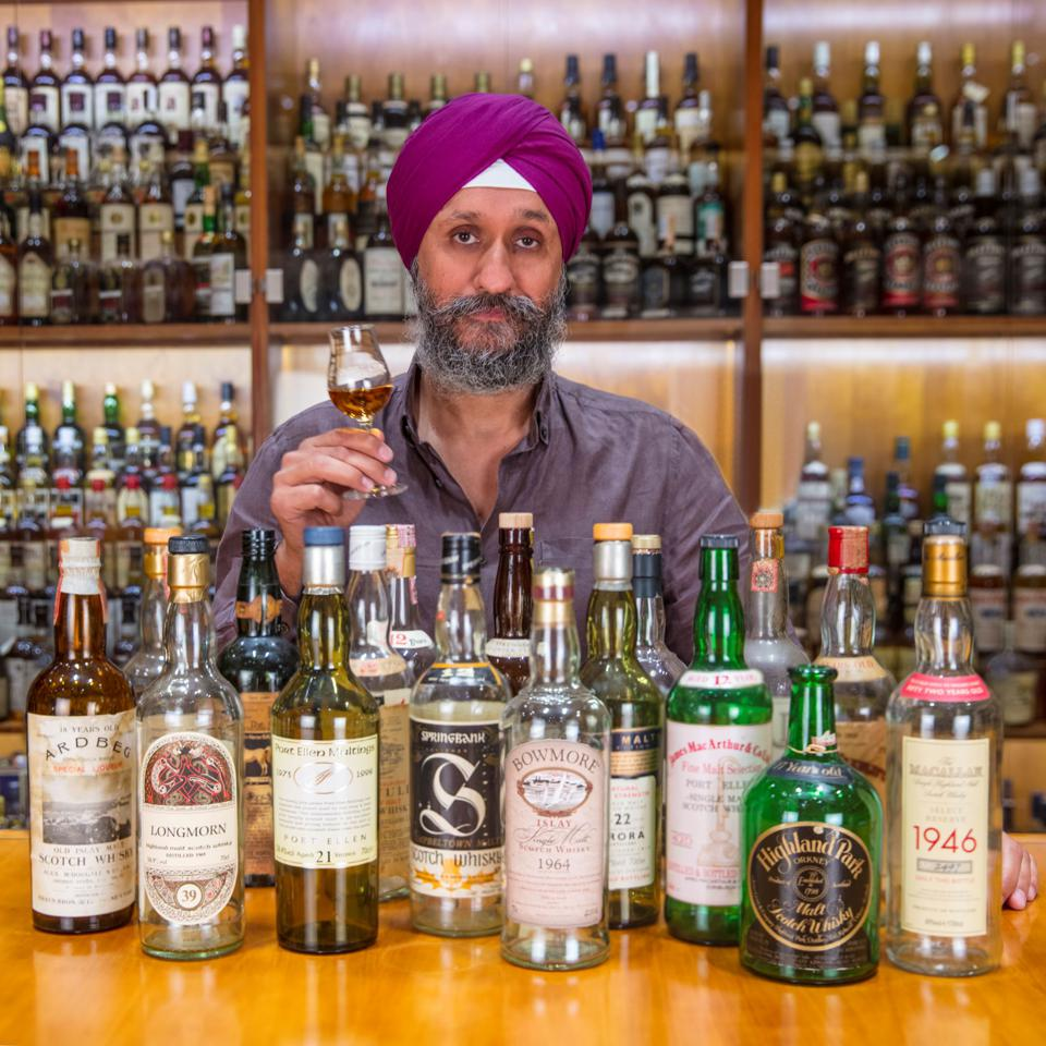 Sukhinder Singh, CEO of The Whisky Exchange surrounded by bottles from his legendary Scotch whisky collection