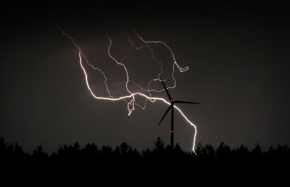 A lightning bolt illuminates the silhouette of a wind turbine during a storm in Bavaria.