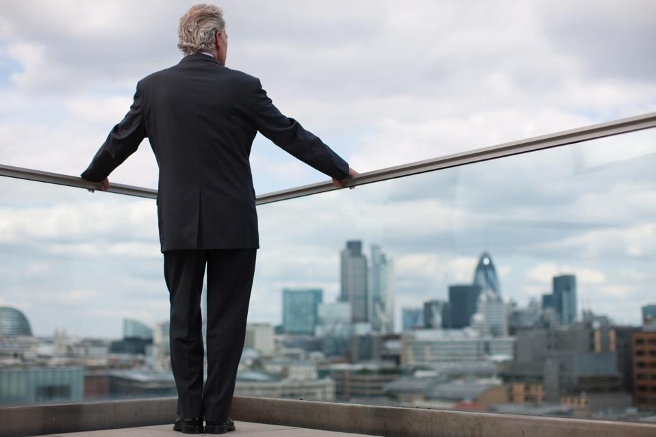 Il vecchio bianco guarda fuori dalla città dal balcone.  Tutto ciò che manca è il fuoco e il violino.