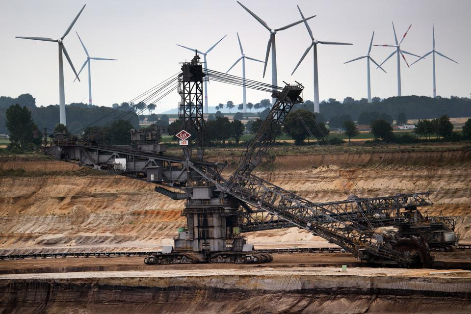 Windmills rotate behind a bucket wheel excavator at a German opencast lignite mine.