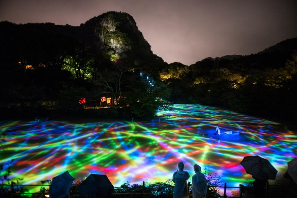 A pond with lights dancing across it in Japan.