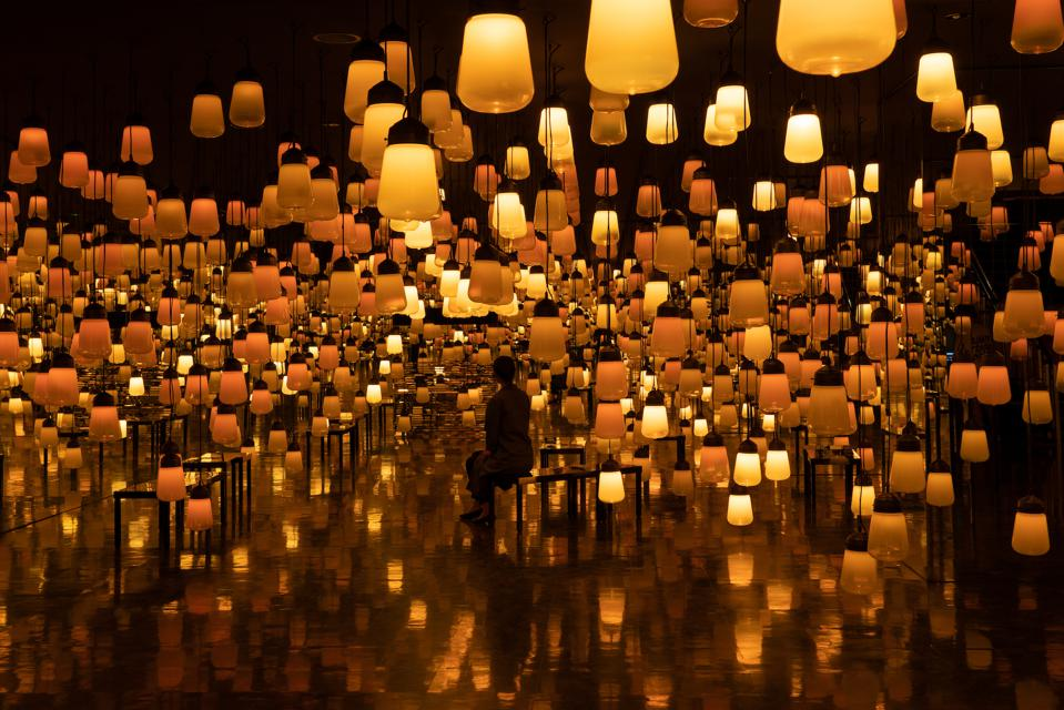 A woman sits in a lantern filled room