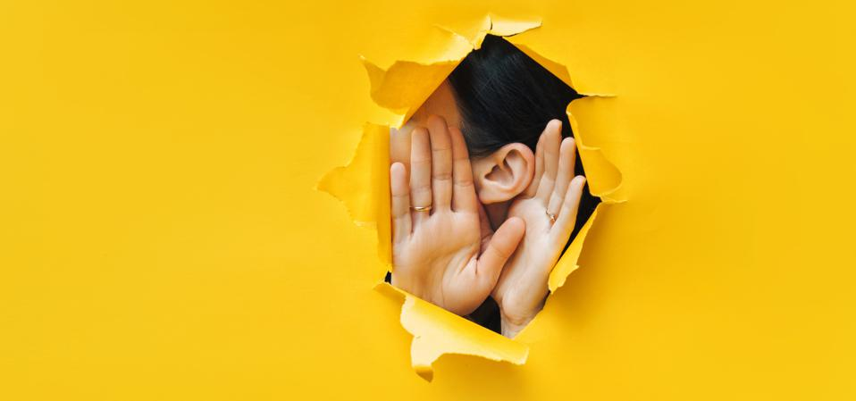 Female ear and hands close-up. Torn paper, yellow background.