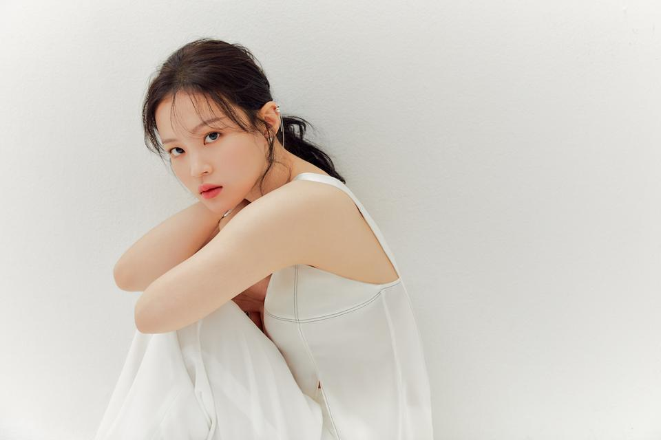 Promotional image of Lee Hi looking at the camera while seated with her arms on her knees wearing a white dress