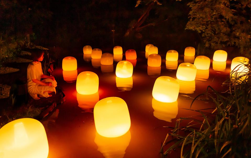 A woman meditates in front of lanterns in Japan