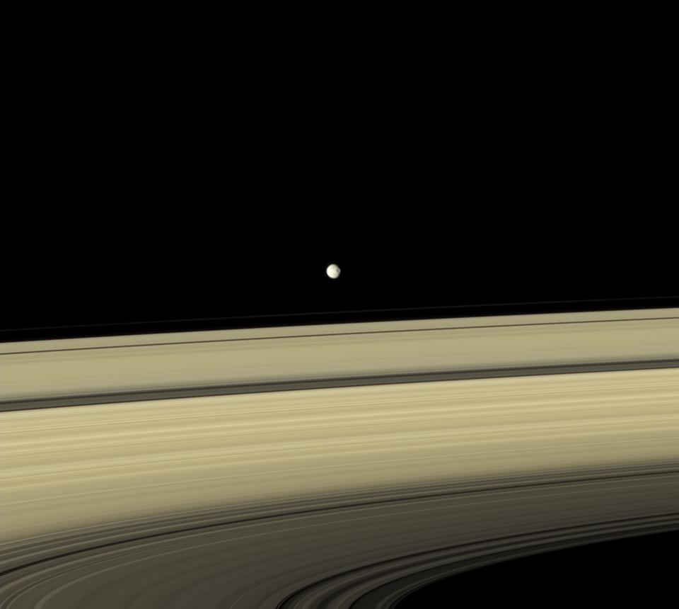 Mimas appears to hover above the colorful rings. Cassini.
