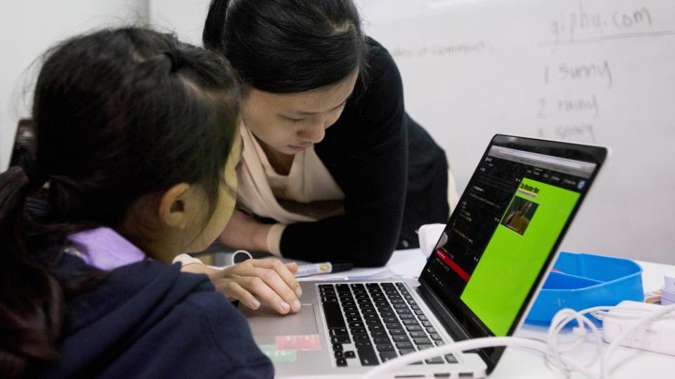 An instructor and a student work on an Apple Inc. laptop computer during a coding class. Photographer: Xaume Olleros/Bloomberg