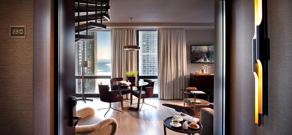 The living room of a suite at the Thompson Chicago with views of the city