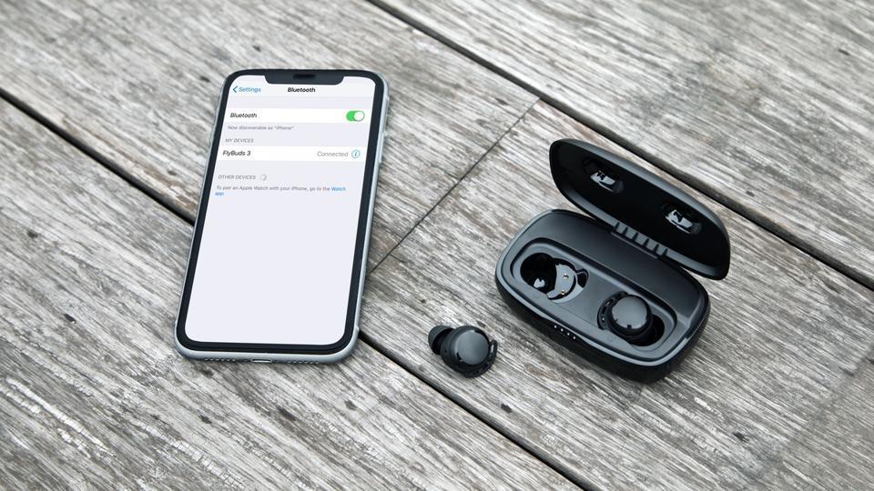 Tribit Flybuds 3 su un tavolo accanto a uno smartphone