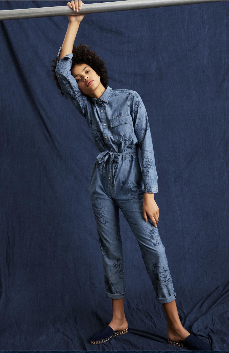 The Print Denim Jumpsuit in Hawaiian floral print boasts a fun yet sophisticated design