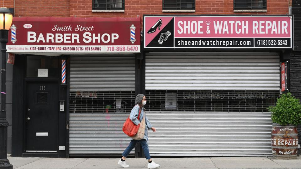 Woman walks past closed businesses in face mask