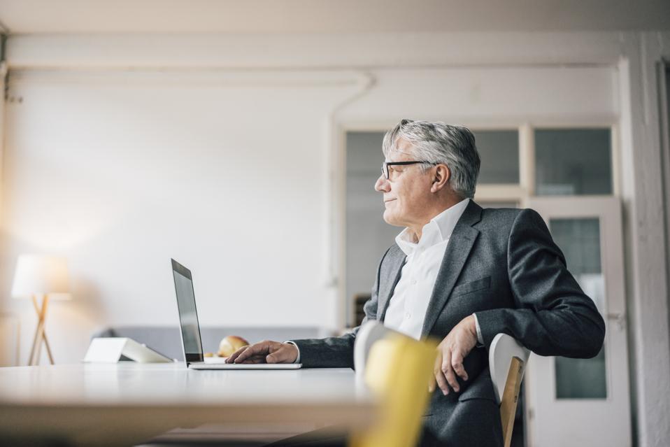 Confident senior businessman using laptop