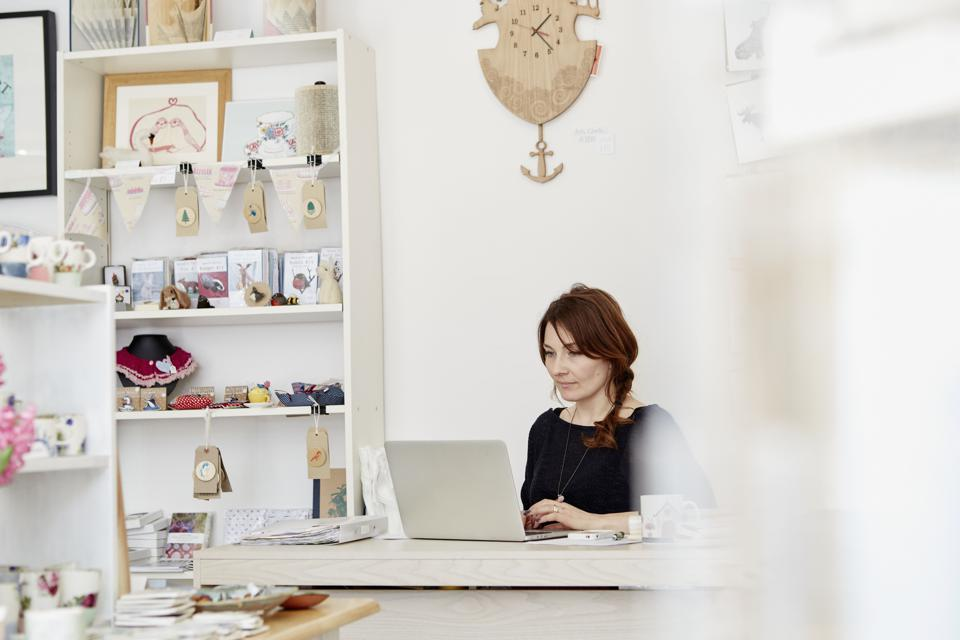 A woman sitting at a desk in a small gift shop, doing the paperwork, managing the business, using a laptop.