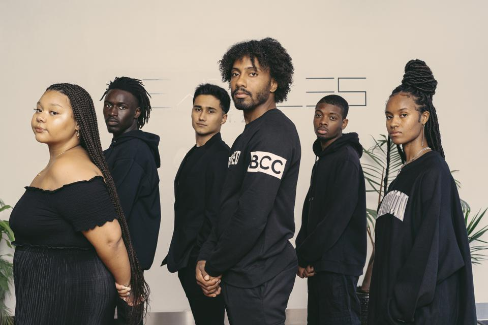 Six young people, all dressed in black, stand with shoulders turned but faces looking at the camera.