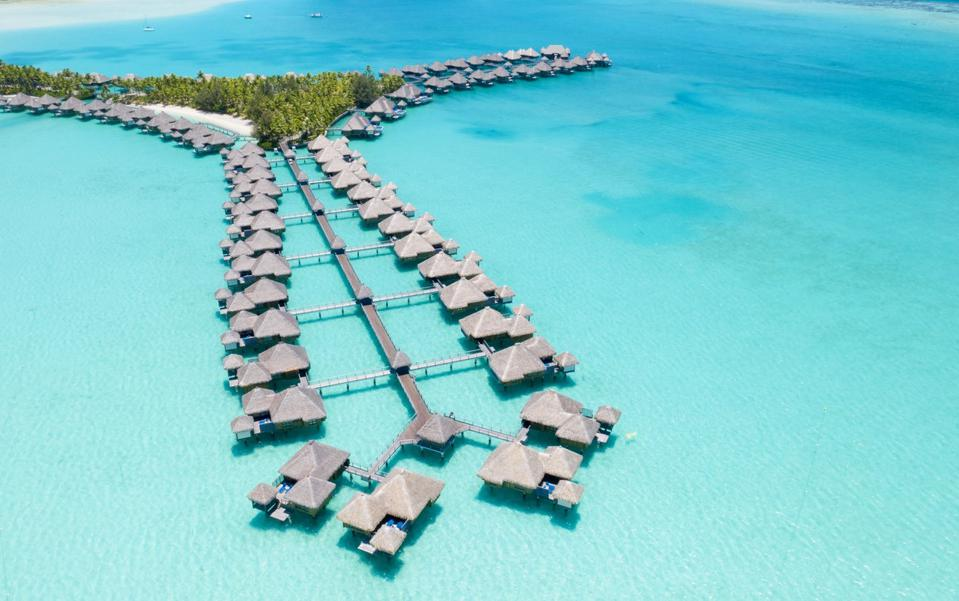 A lineup of thatched cottages suspended over turquoise water in Bora Bora