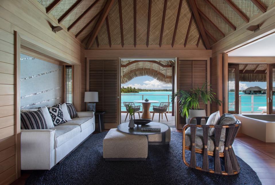 Sharp Polynesian decor within an overwater bungalow looking out at turquoise water