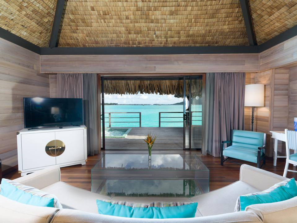 Turquoise and white contemporary furniture within an overwater villa in Bora Bora