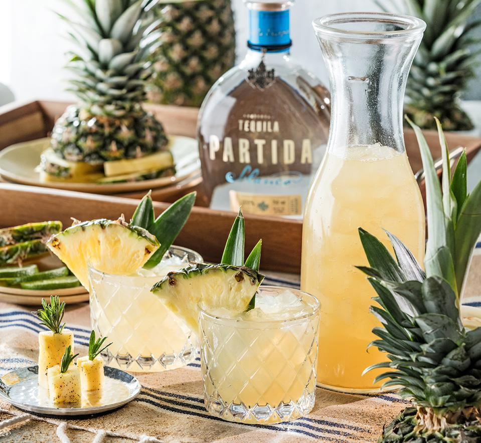 Tequila Partida bottle, pineapples and cocktails in glasses.