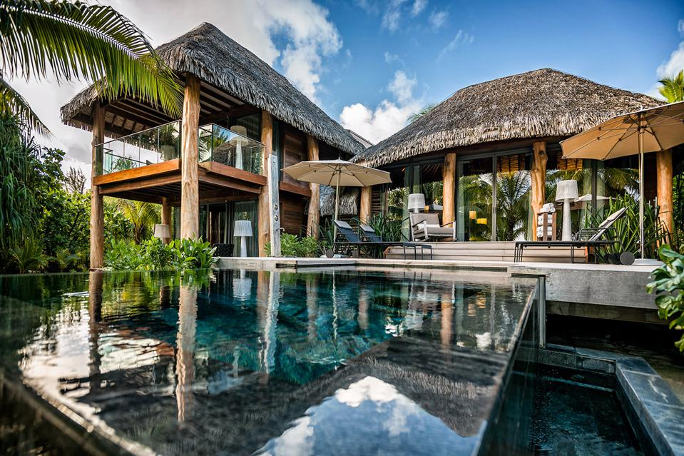 A thatched Polynesian villa and swimming pool