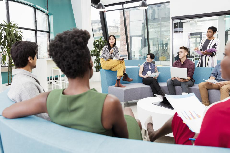 Businesswoman leading informal meeting in modern open plan office